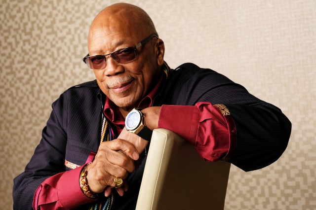 Quincy Jones leaning on the back support of a chair